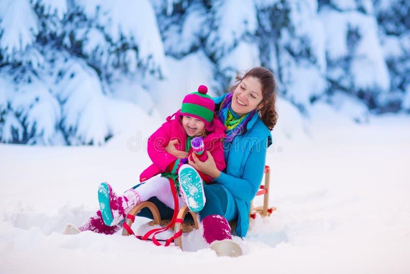 Modern och barnet som sledding i ett snöig, parkerar royaltyfri fotografi