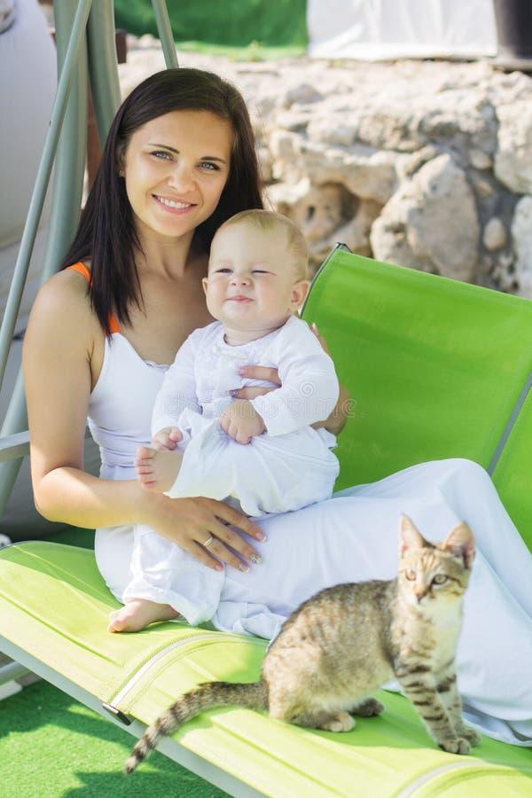 Modern och behandla som ett barn lite pojken med strimmig kattkattungen arkivfoto