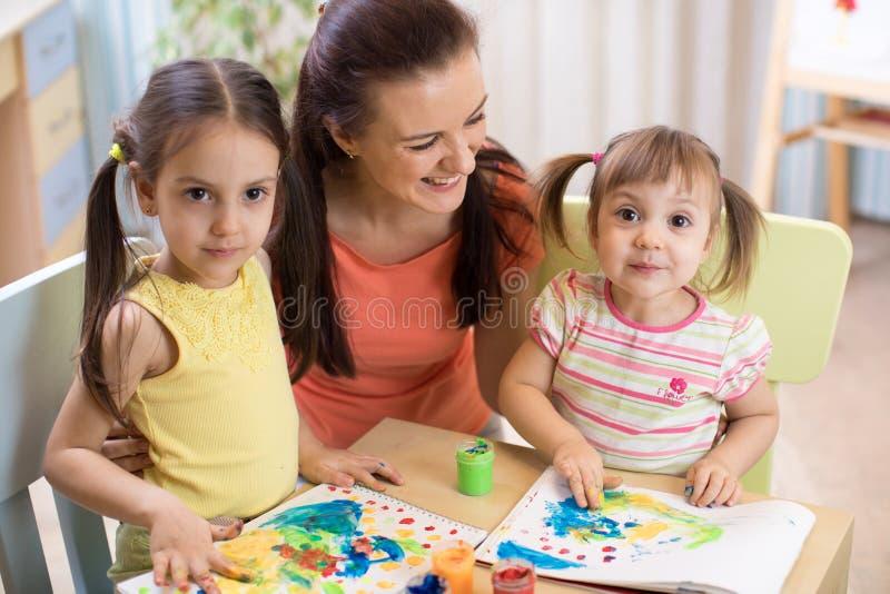 Modern och döttrar målar tillsammans Den lyckliga familjen färgar med målarpenseln Kvinnan och barn har en gyckel royaltyfri fotografi