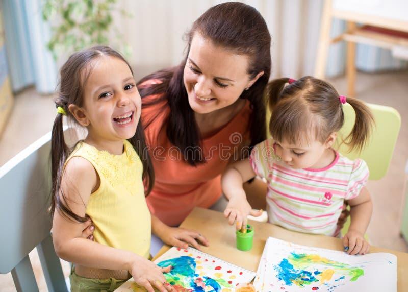 Modern och döttrar målar tillsammans Den lyckliga familjen färgar med målarpenseln Kvinnan och barn har en rolig tidsfördriv arkivfoto