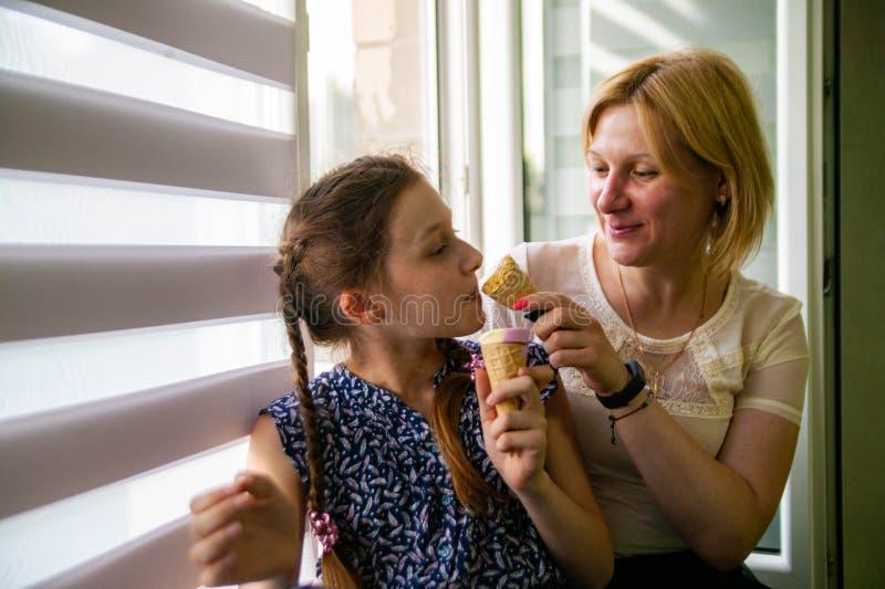 Modern och den gulliga dottern tycker om glass på en varm sommardag fotografering för bildbyråer