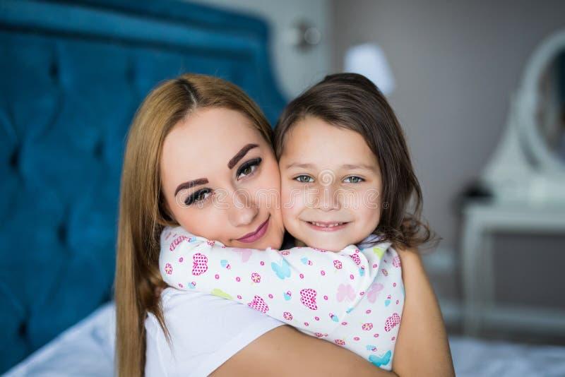 Modern och den lilla dottern tycker om i säng som är hemmastadd och ser kameran fotografering för bildbyråer