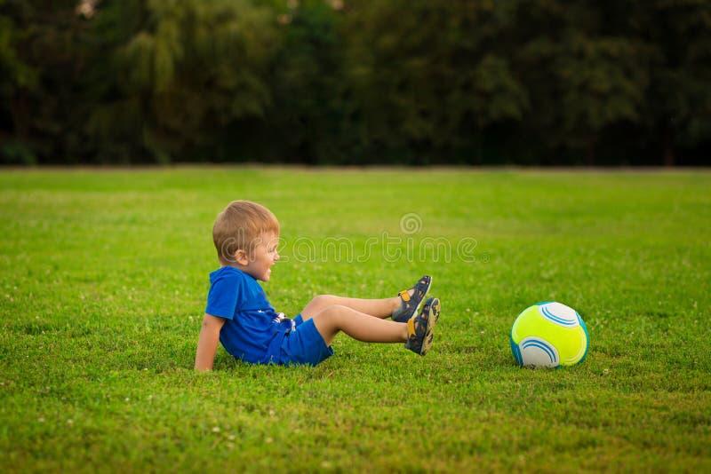 Modern och den lilla sonen som spelar bollen på gräs parkerar in arkivbild