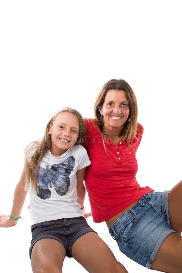 Modern och den unga dottern i ett tillgivet poserar för att sitta på golv på en vit bakgrund arkivfoto