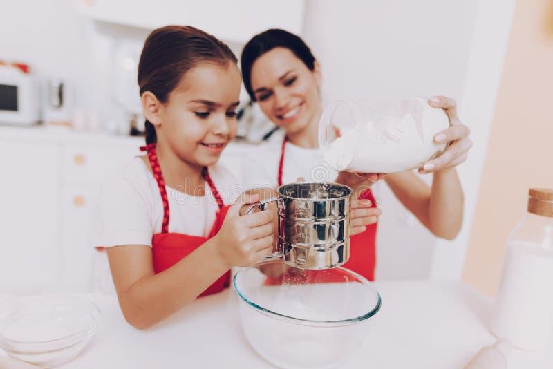 Modern och den unga dottern sipprar mjöl för kaka royaltyfri fotografi