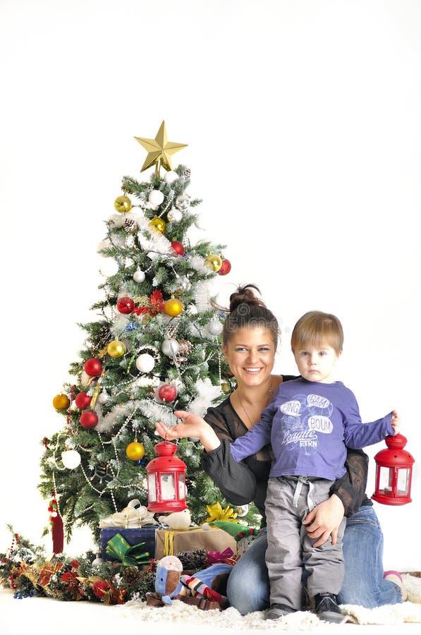 Modern och deras småbarn sitter nära julgranen med röda lampor arkivbild