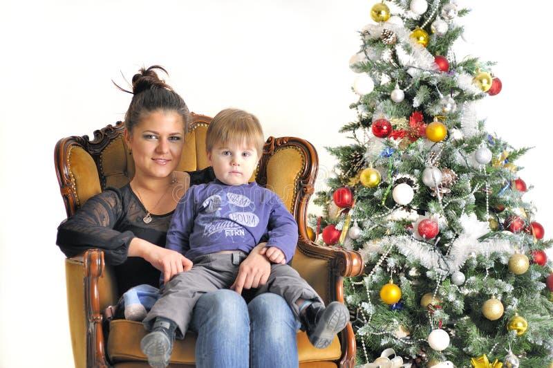 Modern och deras småbarn sitter på stol nära julgranen arkivbild