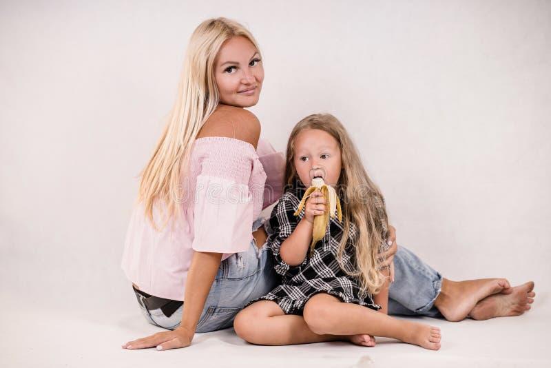 Modern och dottern äter bananen på vit bakgrund royaltyfria foton
