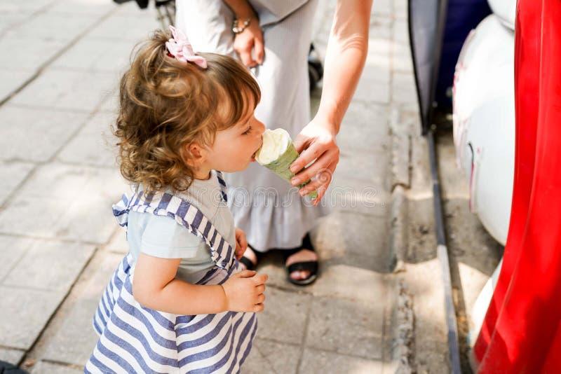 Modern och dottern äter glass under går utomhus royaltyfri foto