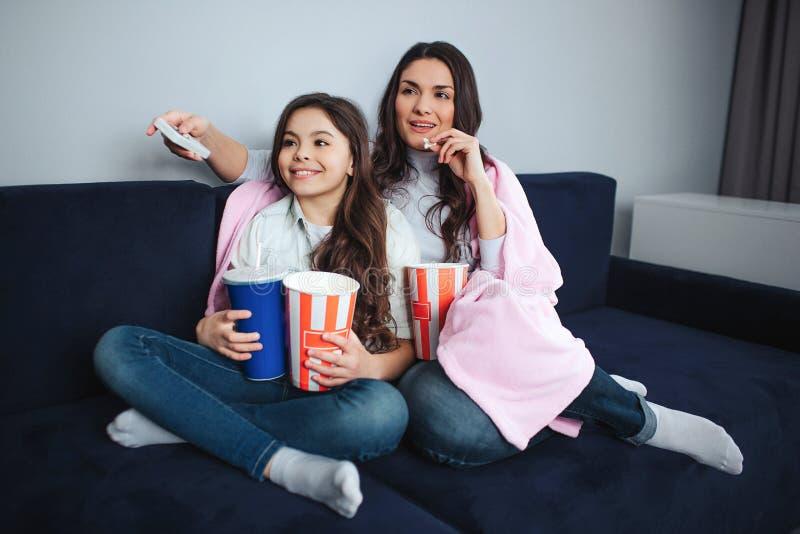 Modern och dottern för härlig brunett sitter den caucasian tillsammans i rum De håller ögonen på film Folket rymmer popcornkorgar fotografering för bildbyråer