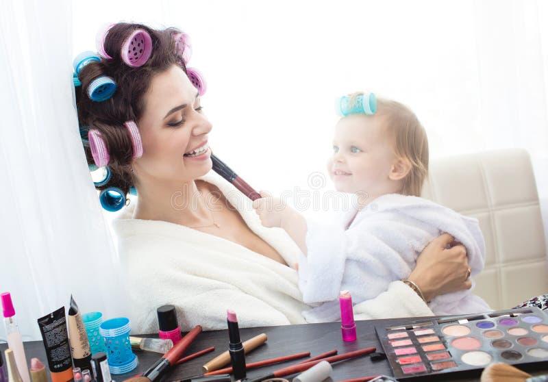 Modern och dottern gör hår, manikyrer, makeup och att ha gyckel fotografering för bildbyråer