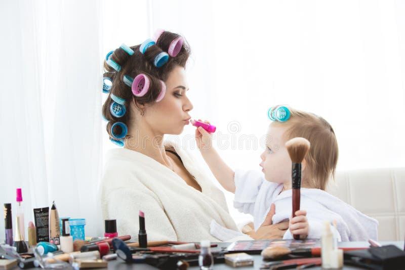 Modern och dottern gör hår, manikyrer, makeup och att ha gyckel arkivbild
