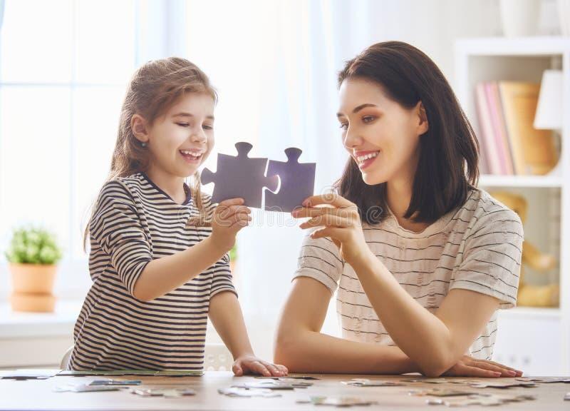 Modern och dottern gör pussel arkivbilder