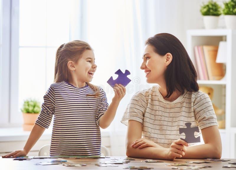 Modern och dottern gör pussel royaltyfria bilder