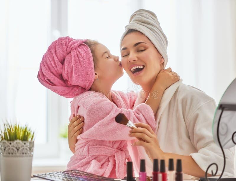 Modern och dottern gör smink arkivfoto