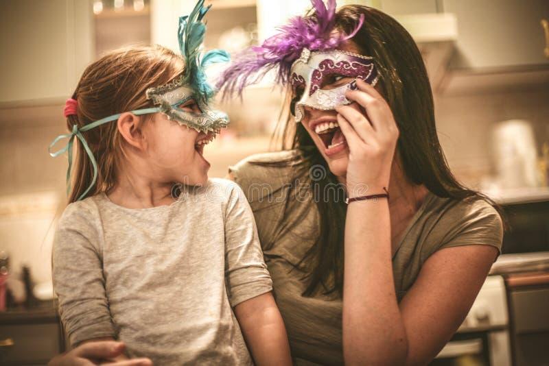 Modern och dottern har lek med karnevalmaskeringen royaltyfri bild