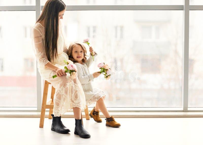 Modern och dottern har roligt anseende nära ett enormt fönster, daen royaltyfria foton
