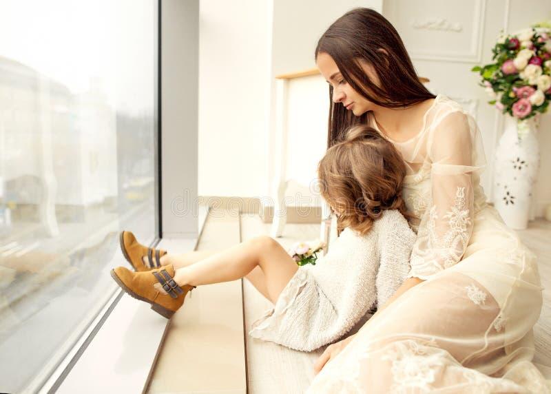 Modern och dottern har roligt anseende nära ett enormt fönster, daen royaltyfri bild