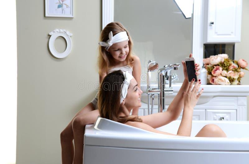 Modern och dottern i ett badrumbad badar att spela med lyckligt le för mobil mobiltelefon royaltyfri foto
