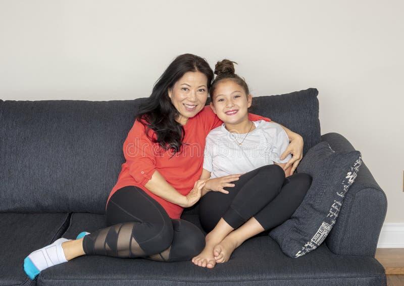 Modern och dottern i ett tillgivet poserar på en soffa arkivfoto