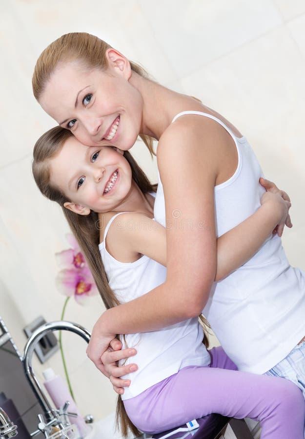 Modern och dottern kramar varje annan i badrum royaltyfri foto