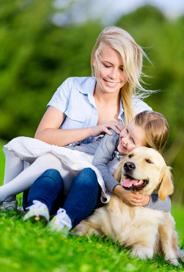 Modern och dottern med apportörn är på gräset royaltyfri bild