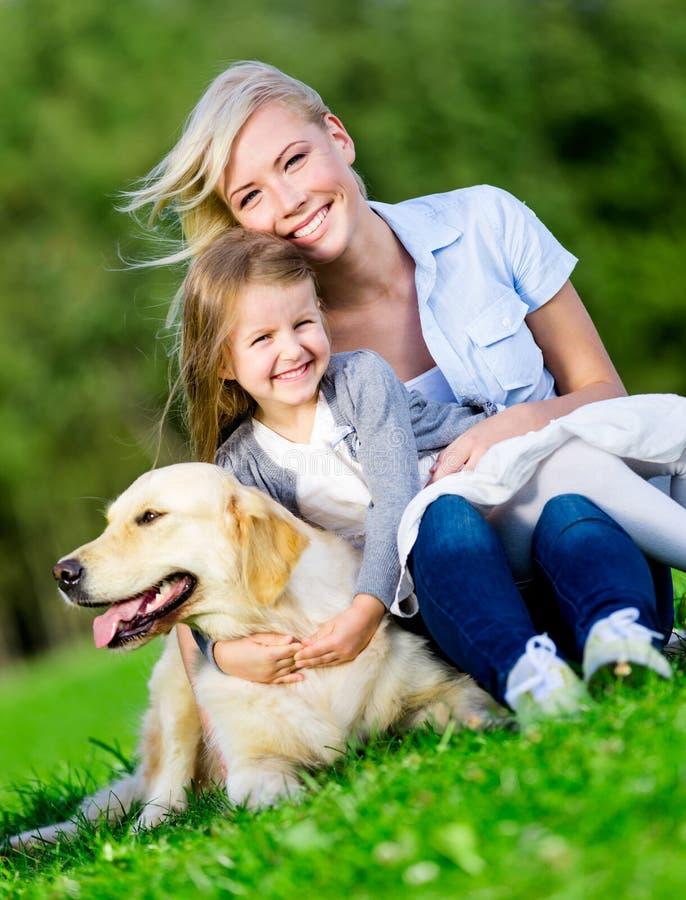 Modern och dottern med hunden är på gräset royaltyfria foton