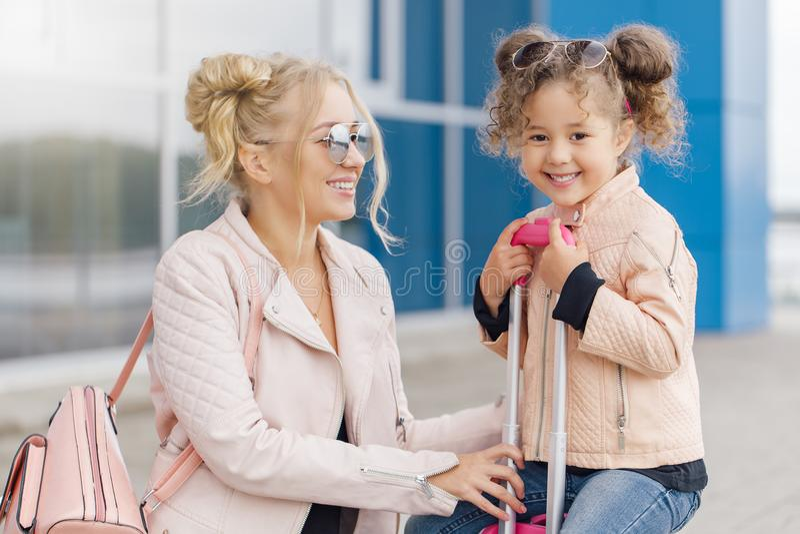 Modern och dottern med rosa bagage i rosa färger klår upp mot flygplatsen arkivbild