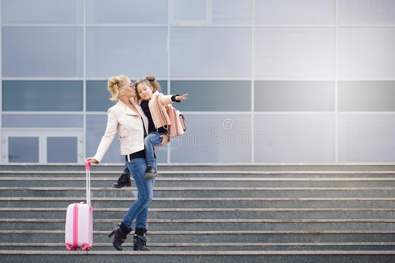 Modern och dottern med rosa bagage i rosa färger klår upp mot flygplatsen royaltyfria bilder