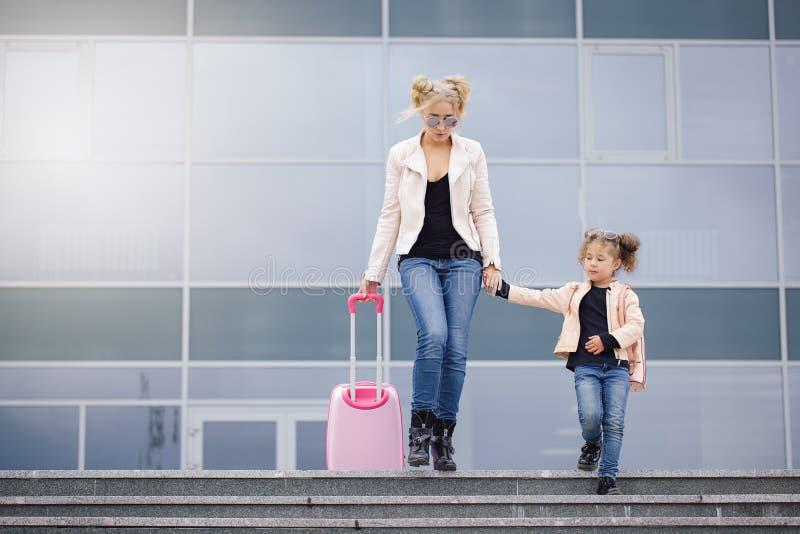 Modern och dottern med rosa bagage i rosa färger klår upp mot flygplatsen royaltyfri fotografi