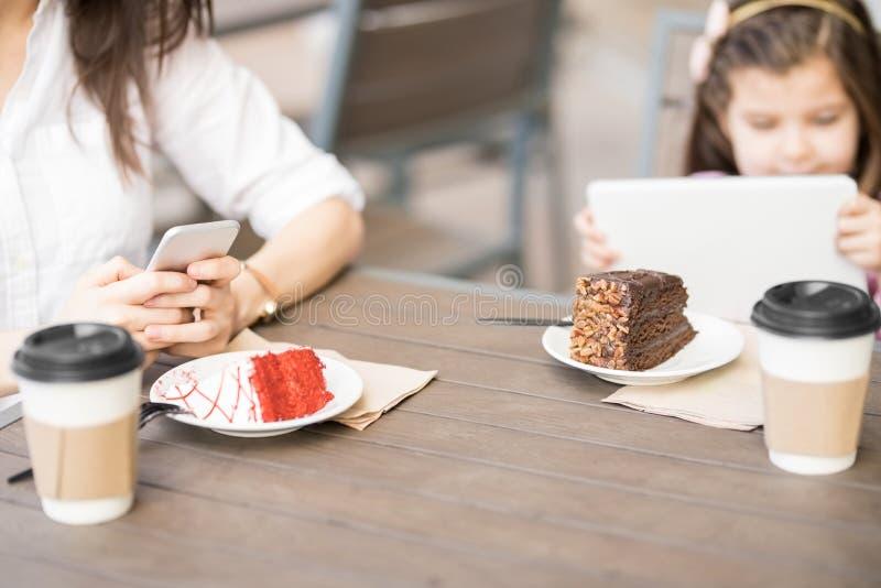 Modern och dottern på kafét bordlägger genom att använda digitala apparater arkivbild