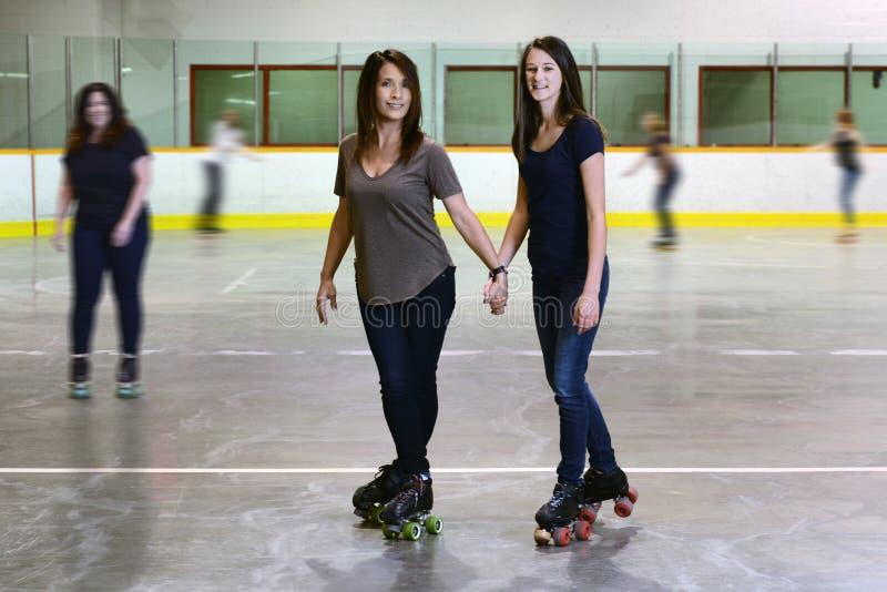 Modern och dottern på rullen som åker skridskor isbanan, fokuserar på mamma royaltyfri bild