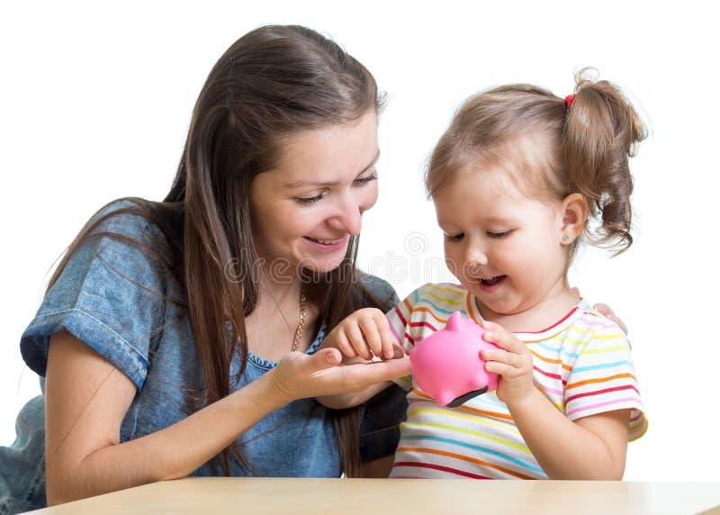 Modern och dottern satte mynt in i spargrisen royaltyfri foto