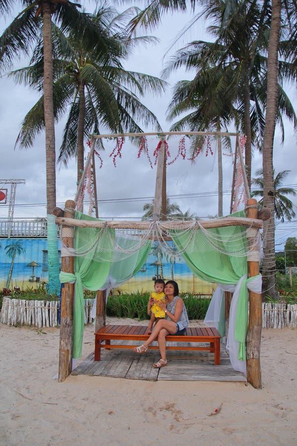 Modern och dottern sitter på bänken med trevlig säng, kokosnöten och stranden royaltyfri foto