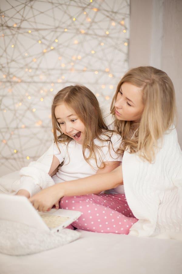 Modern och dottern sitter på säng i pyjamas och har gyckel, använder bärbara datorn livsstil lycklig familj Utbildning lär royaltyfria foton