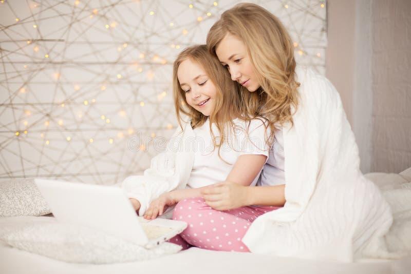Modern och dottern sitter på säng i pyjamas och har gyckel, använder bärbara datorn livsstil lycklig familj Utbildning lär royaltyfri foto