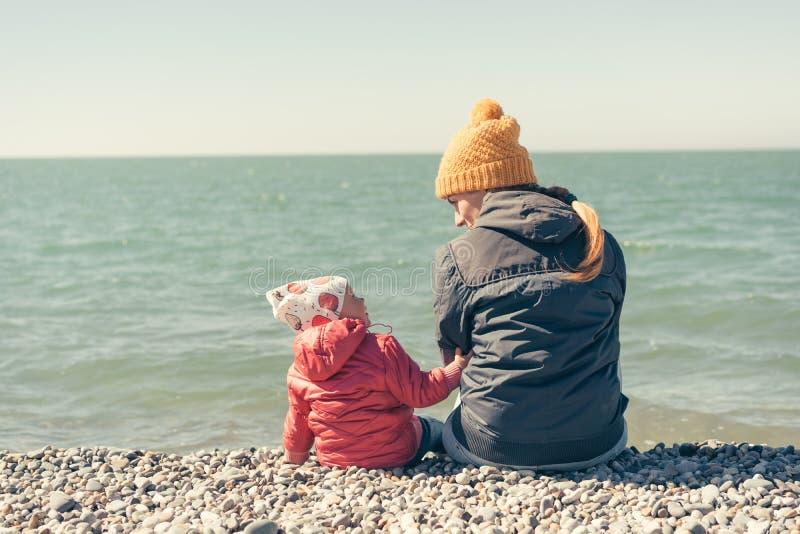 Modern och dottern sitter p? stranden fotografering för bildbyråer