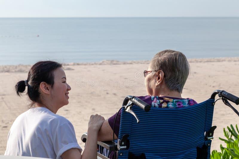 Modern och dottern sitter tillsammans främst av stranden som ser de fotografering för bildbyråer