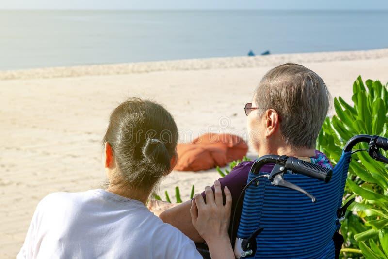 Modern och dottern sitter tillsammans främst av stranden som ser havet arkivbild