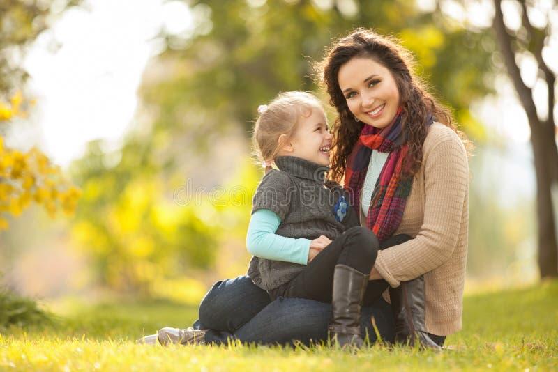 Modern och dottern som går i hösten, parkerar royaltyfri foto