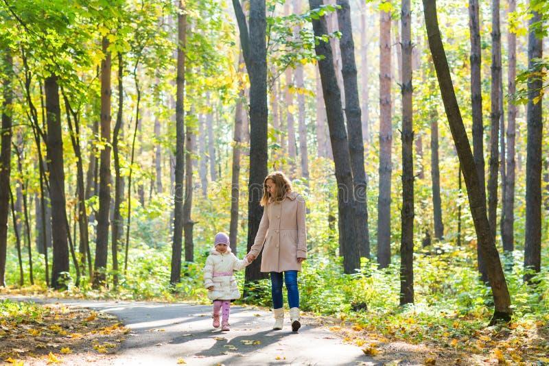 Modern och dottern som går i hösten, parkerar royaltyfria bilder