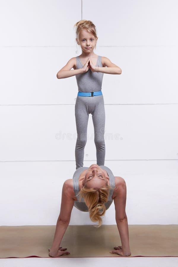Modern och dottern som gör yoga, övar, kondition, idrottshallen som bär den samma bekväma parade kvinnan p för träningsoverallfam royaltyfria bilder
