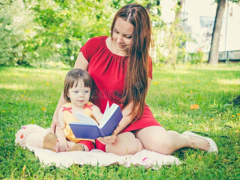 Modern och dottern som läser en bok på, parkerar royaltyfria bilder