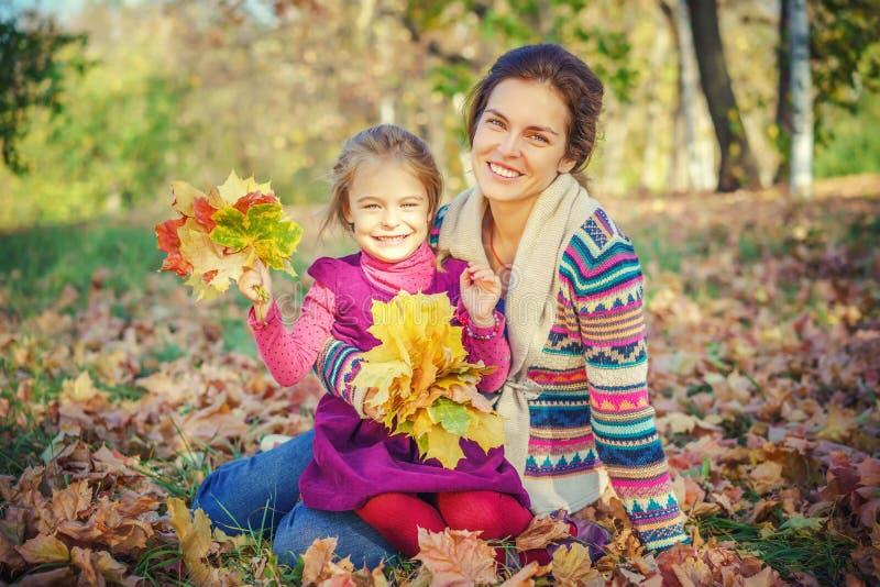 Modern och dottern som spelar i h?st, parkerar arkivbilder