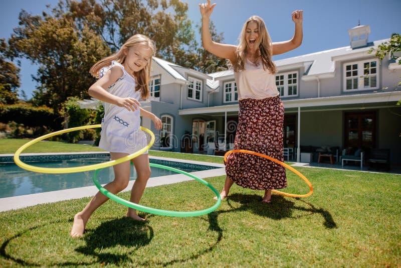 Modern och dottern som spelar med hula, förenar i deras trädgård arkivbild