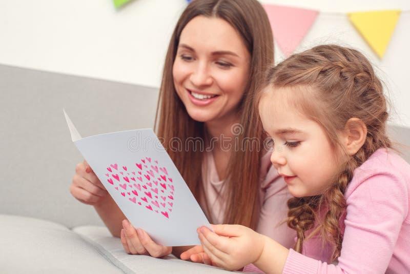 Modern och dottern tillbringar veckoslutet tillsammans hemma på läs- hälsningkort för soffa royaltyfri foto