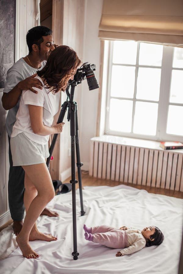 Modern och fadern som tar foto av a, behandla som ett barn flickan som ligger på golvet arkivbild