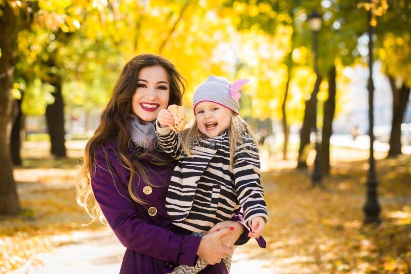Modern och hennes barnflicka som tillsammans spelar på höst, går i natur utomhus fotografering för bildbyråer