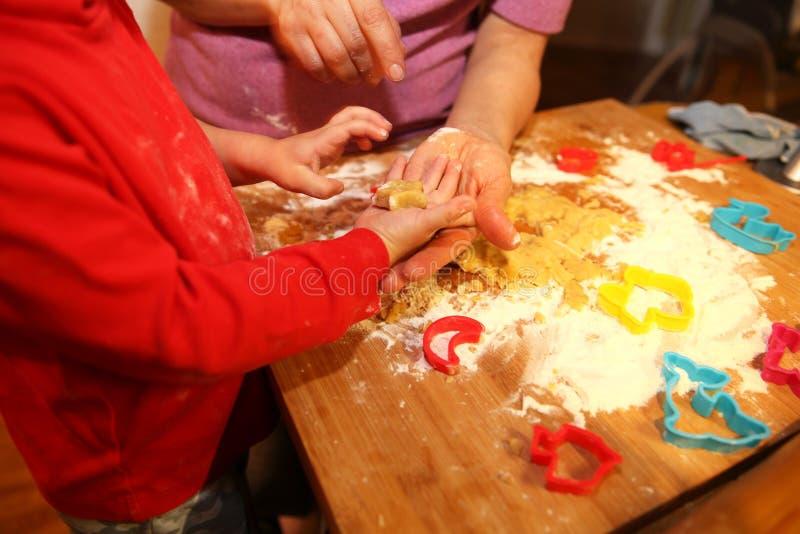 Modern och hennes behandla som ett barn lite göra handkakor hemma i köket arkivfoton