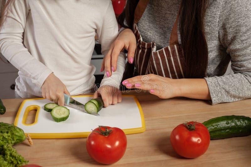 Modern och hennes dotter gör en grönsaksallad och har gyckel på köket fotografering för bildbyråer